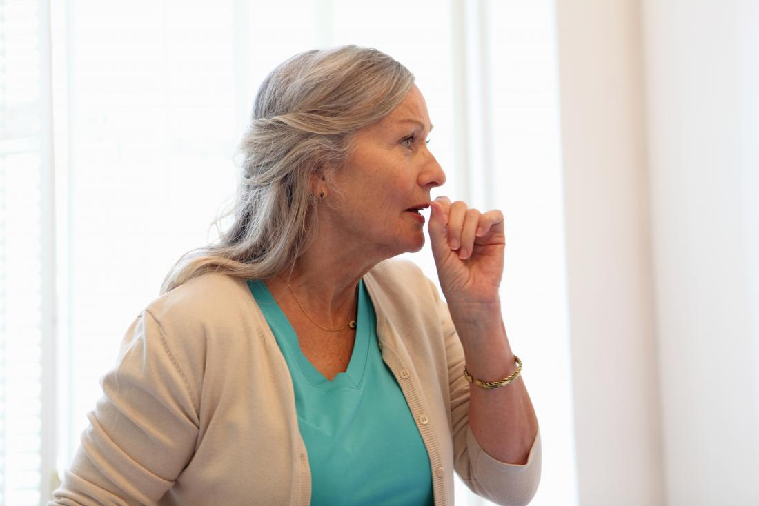 Woman holding hand in front of mouth coughing or clearing throat