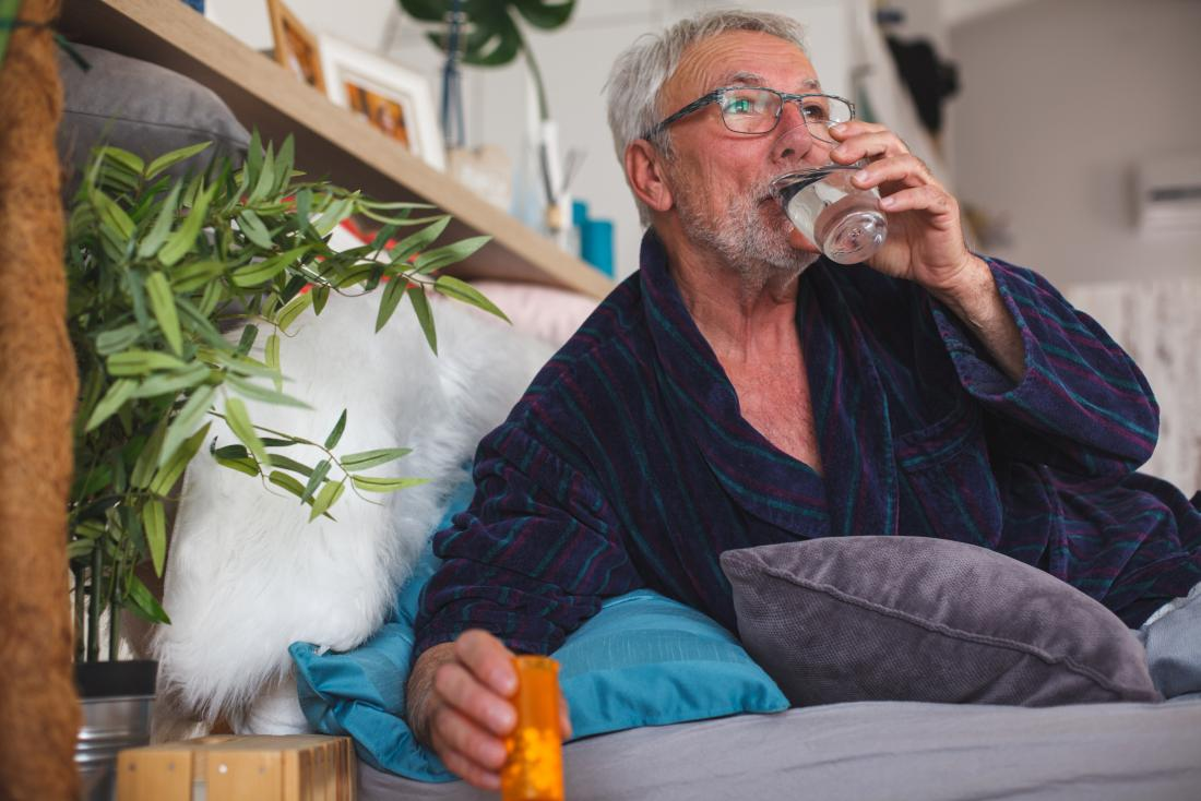 Senior man in bed taking prescription medication statin pills and drinking water