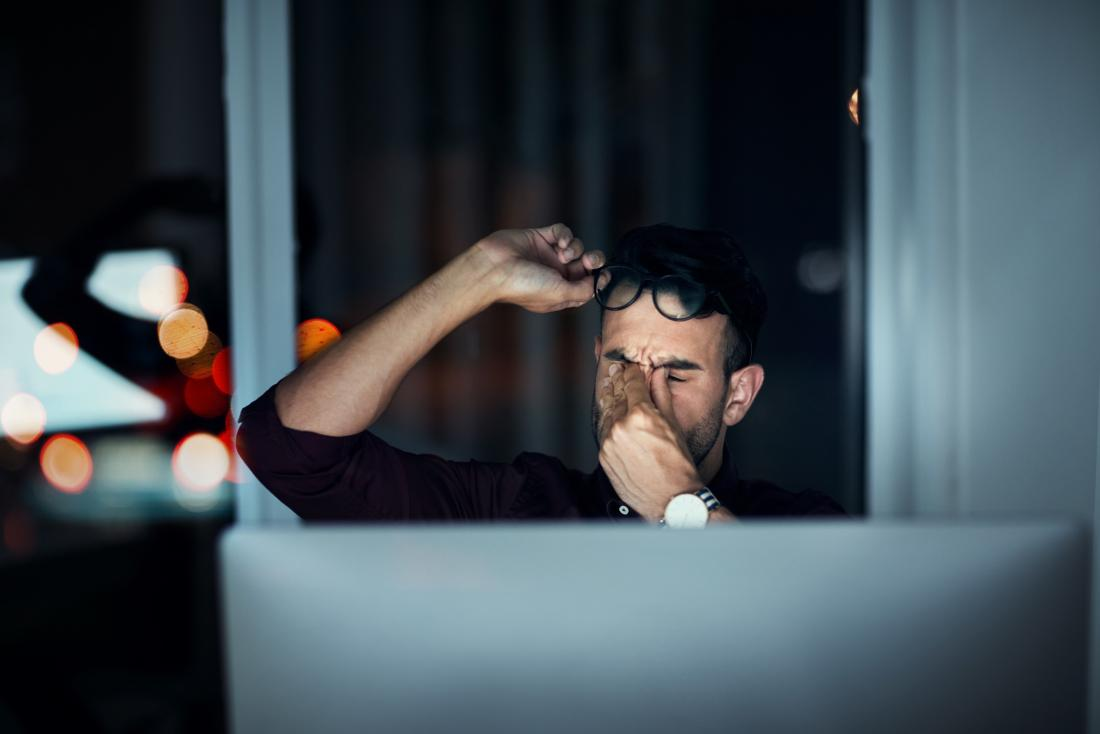 man looking tired in front of their computer