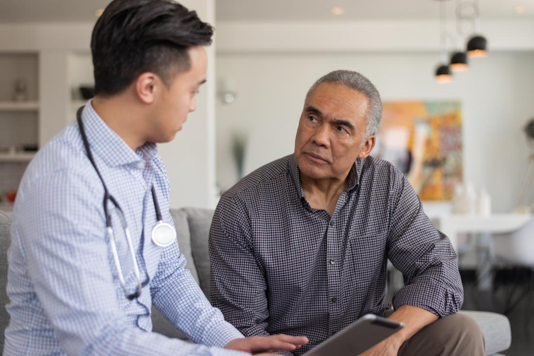 asian doctor talking to male patient