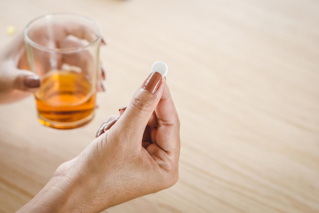 Woman holding a prednisone pill and a glass of alcohol