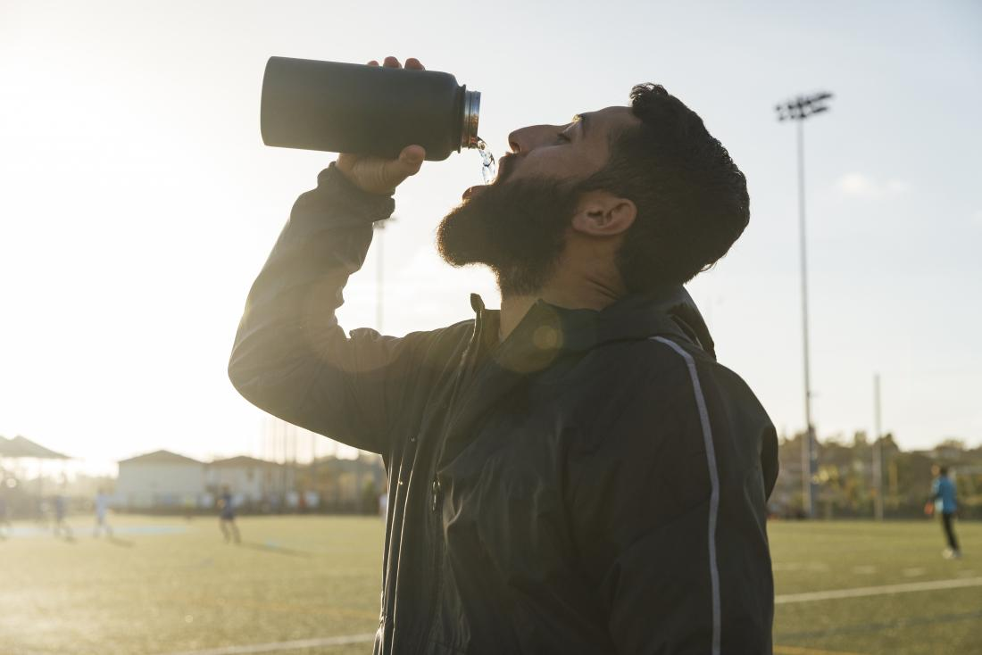Athlete drinking water from bottle while playing sports