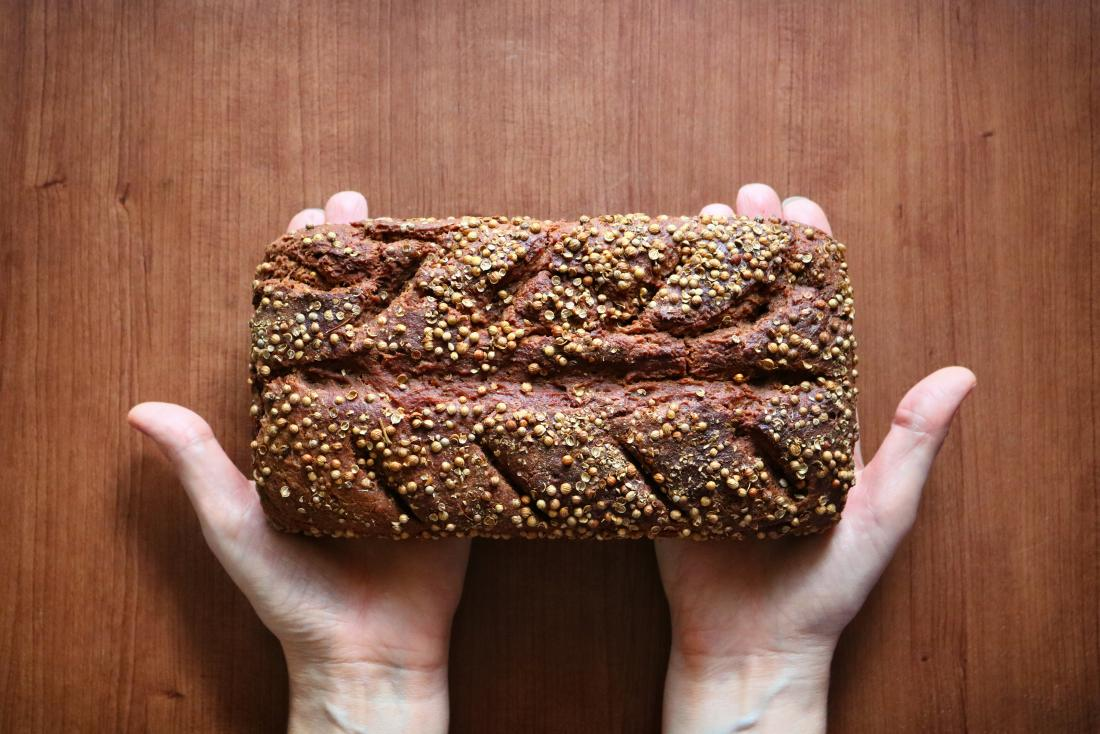 hands holding a loaf of rye bread