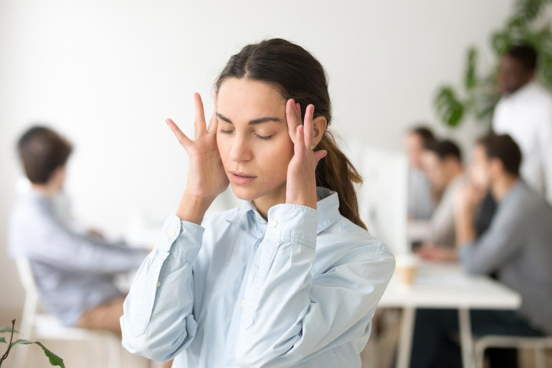Woman holding her head due to dizziness and loss of balance