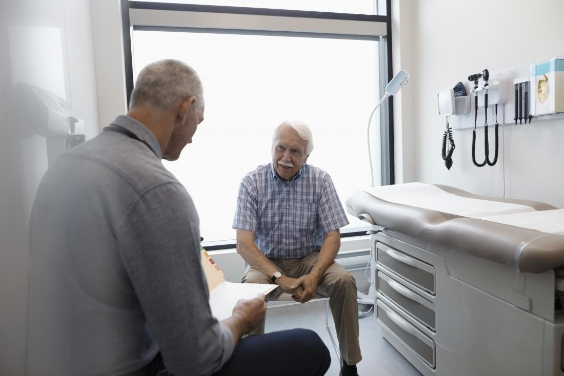 Senior man sitting in doctor's office while gp looks at notes