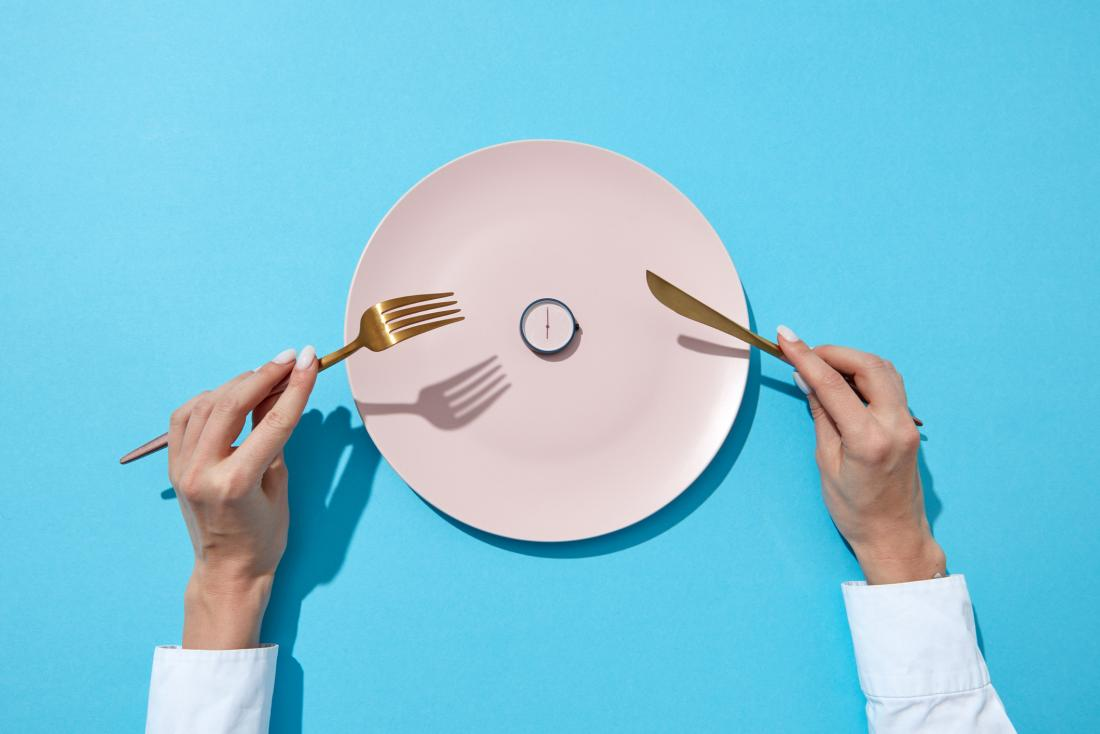 close up of woman's hands holding cutlery and getting ready to eat a watch on a plate