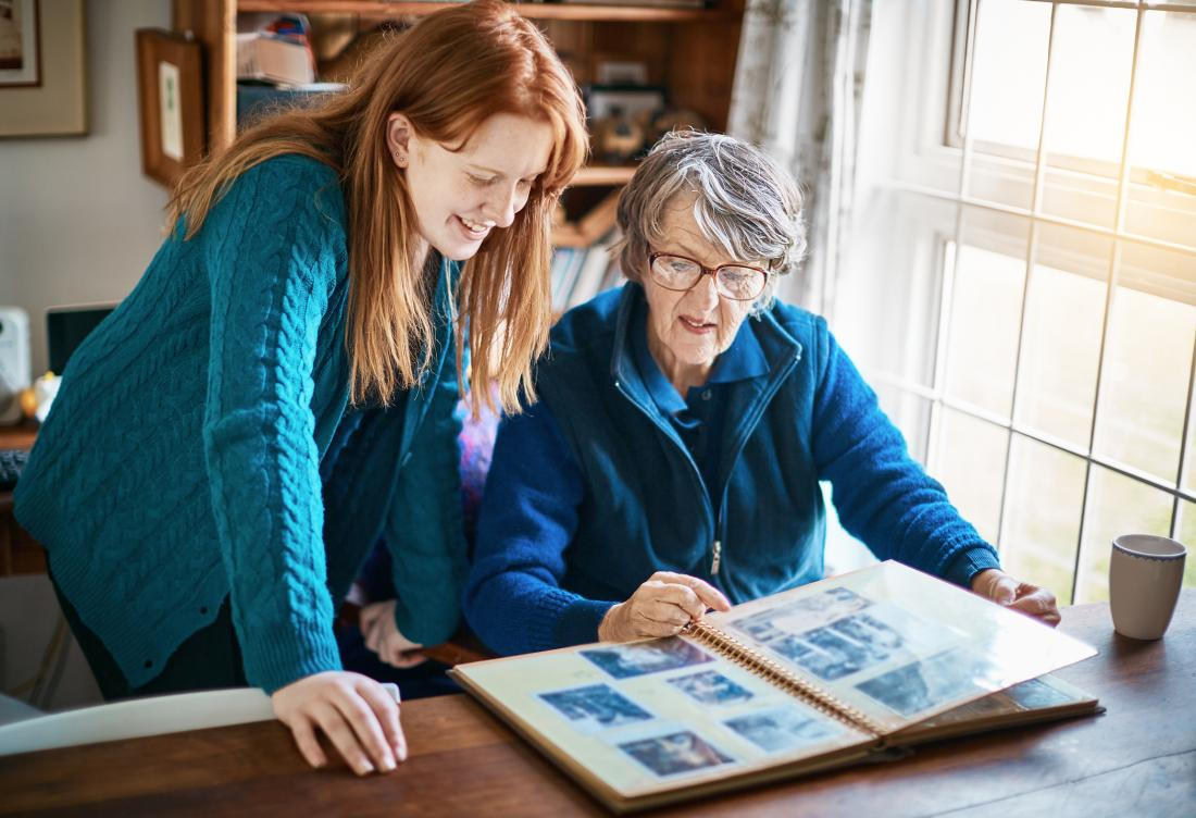 senior woman going through old photo albums with daughter