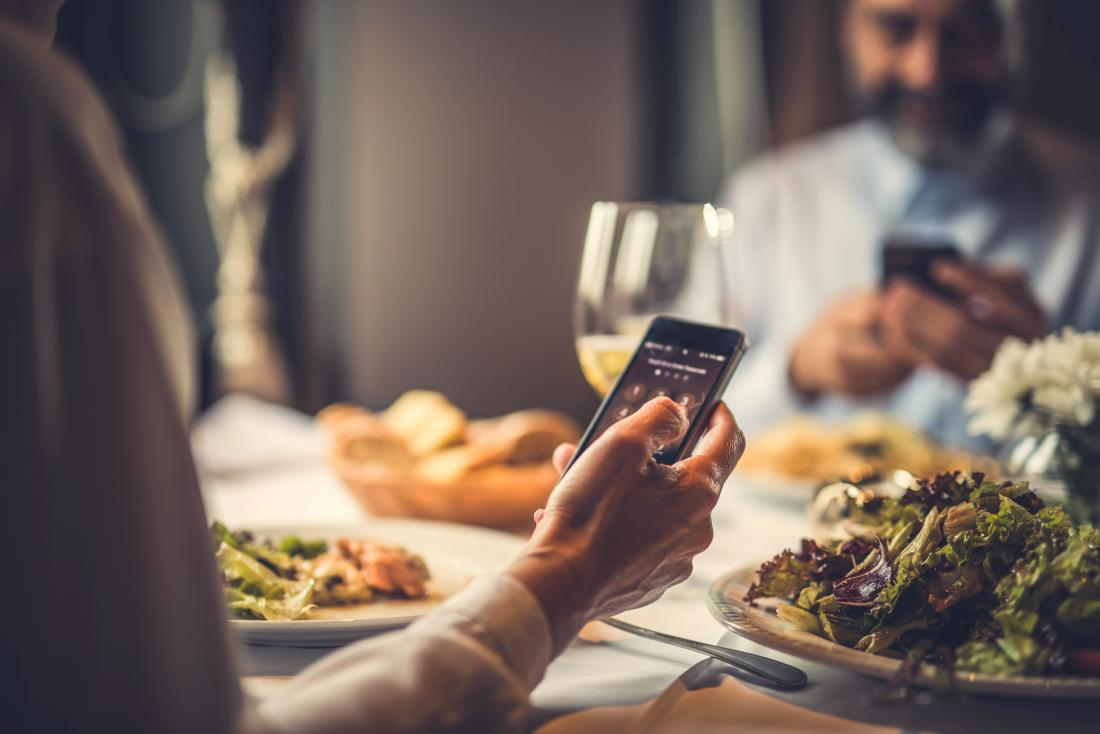 Couple looking at their phones whilst eating