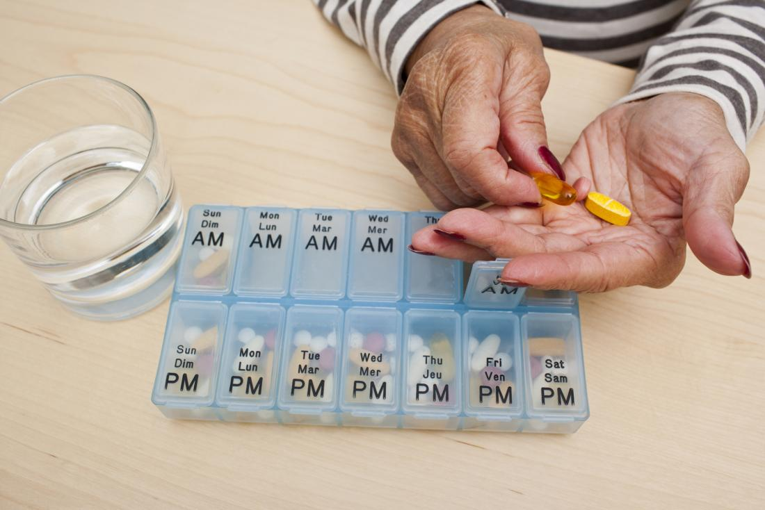 close up of senior woman's hands taking pills