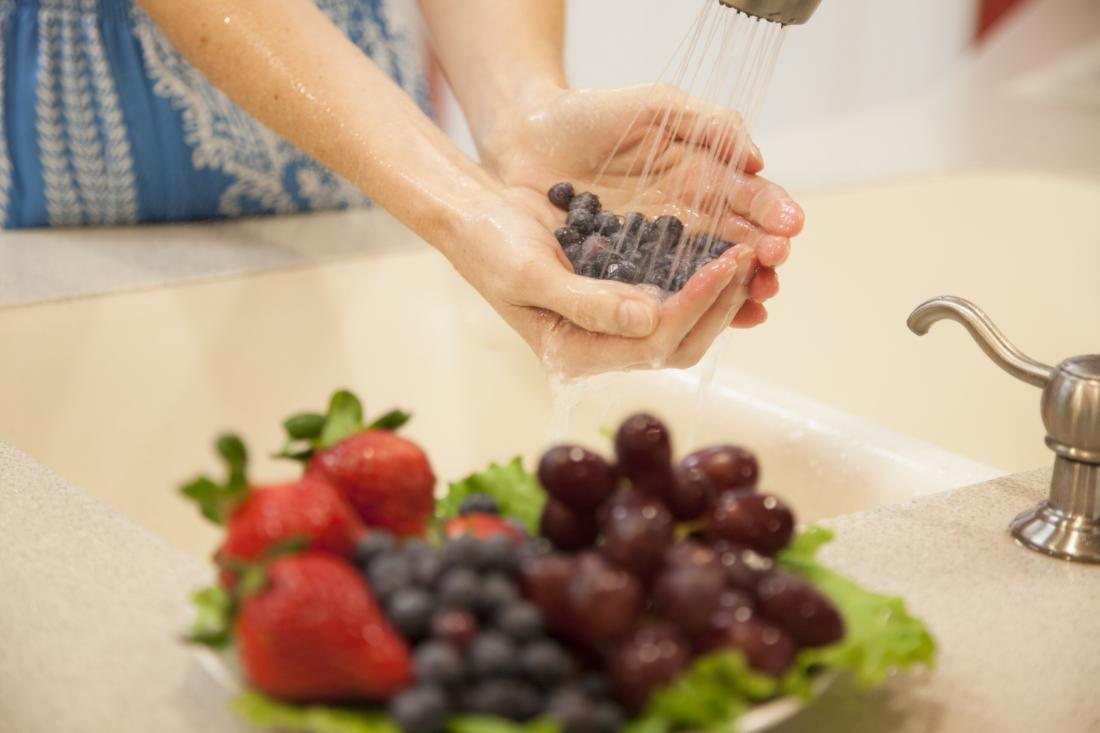 close up of woman's hands washing fruit