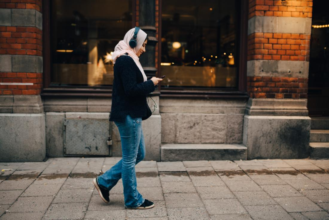 Woman walking in city listening to headphones looking at phone