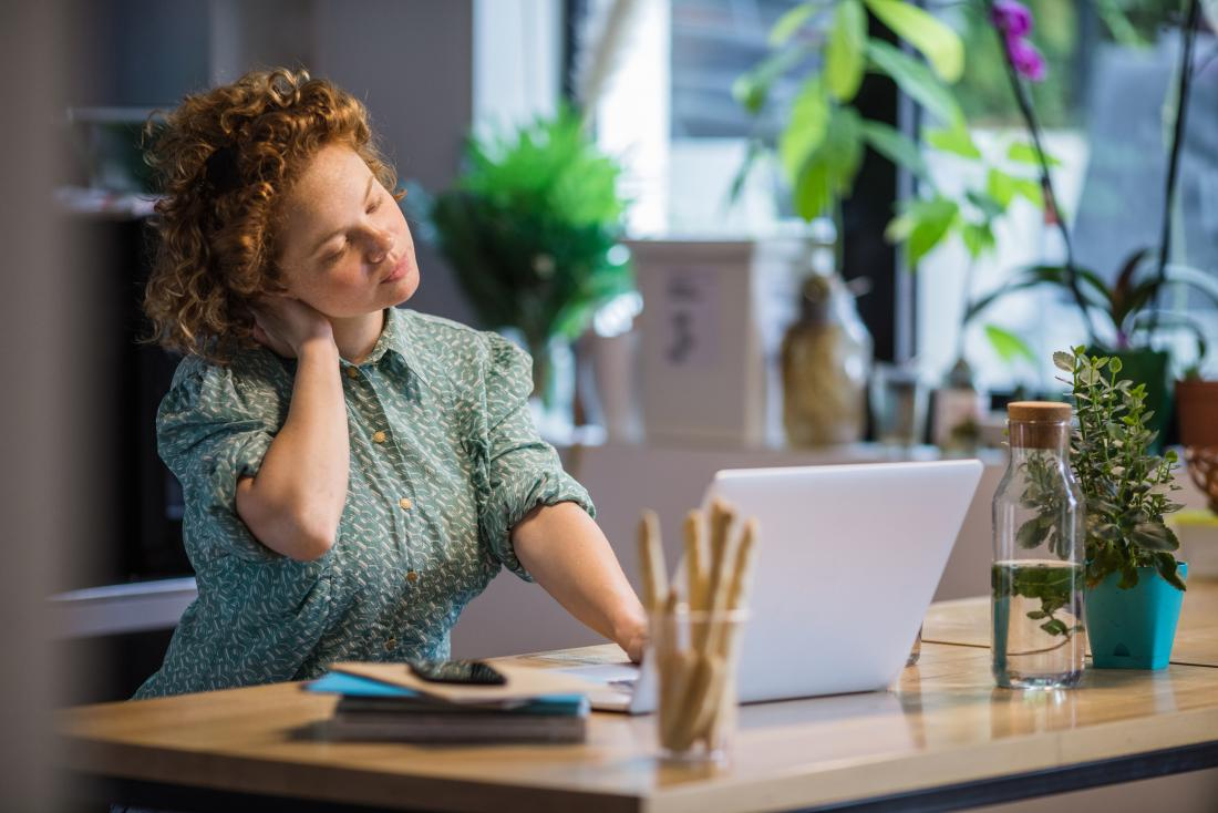 Woman cracking sore neck at desk in office.