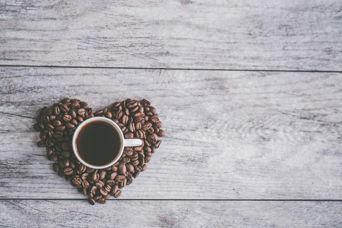 coffee cup in a heart made from coffee beans