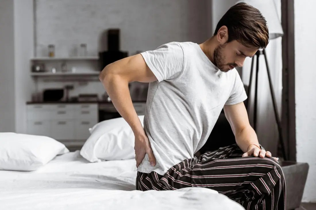 Man with lower back pain and testicle pain sitting on bed.
