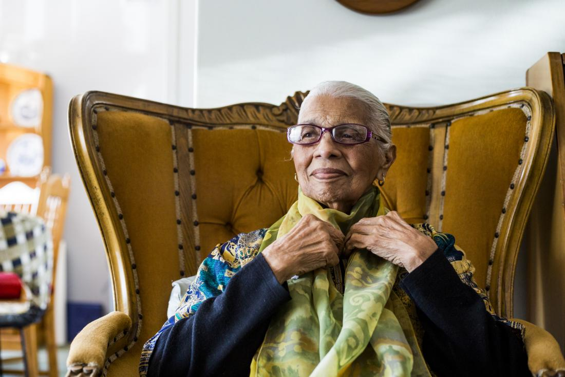 older bespectacled woman sitting in an armchair