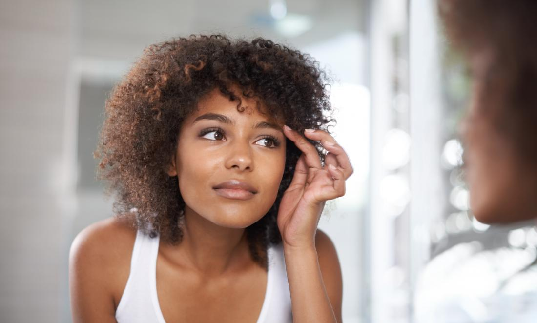 Woman looking at her eyebrows in the mirror