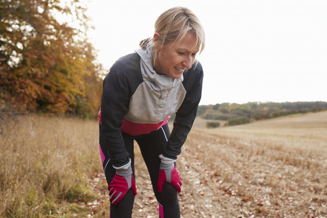 Woman outdoors out of breath in running gear experiencing exercise induced asthma.