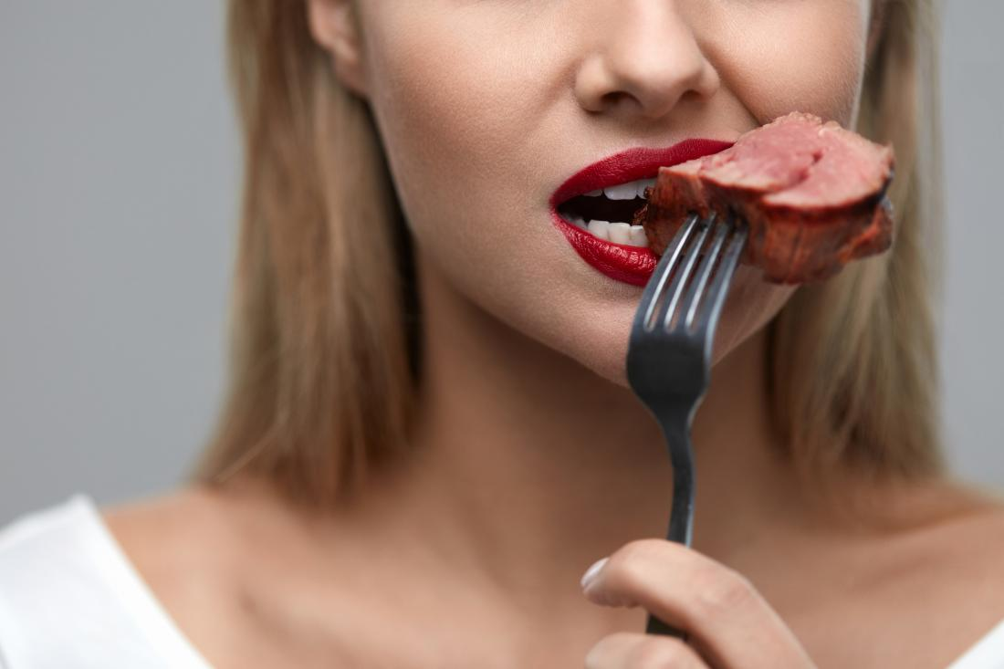 close up of woman's mouth eating red meat