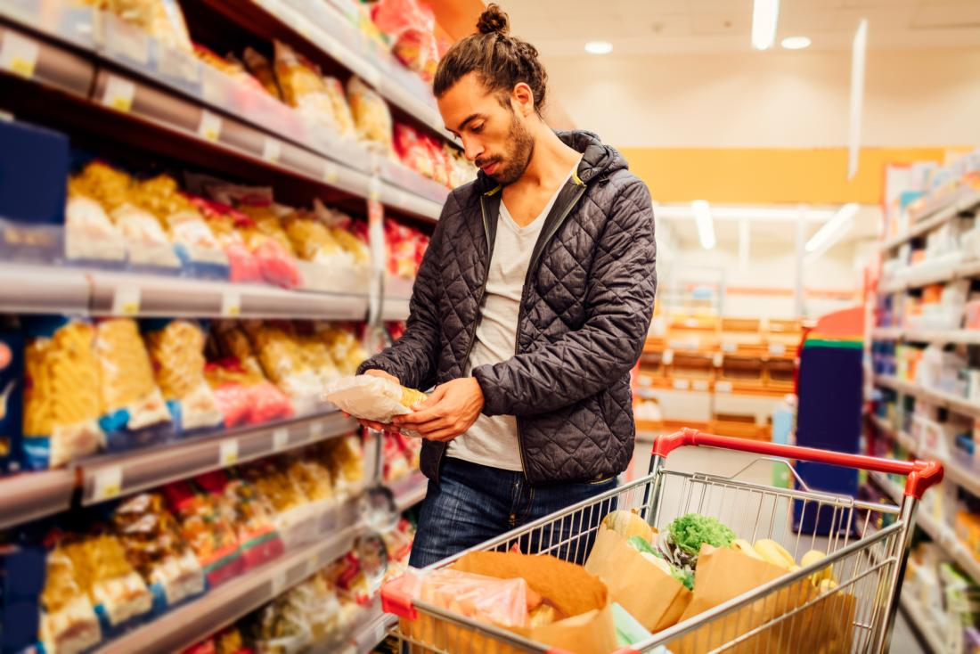 man in supermarket reading nutrition label