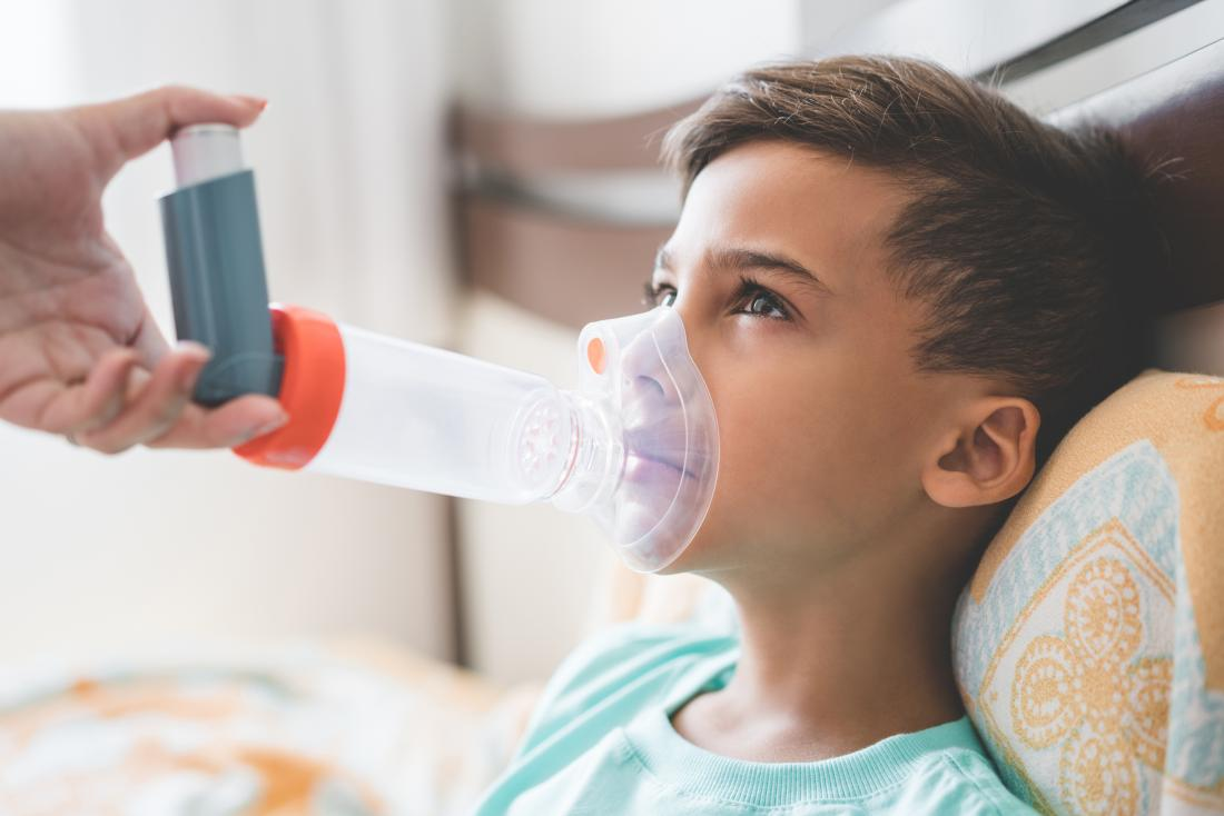 child using asthma inhaler spacer.