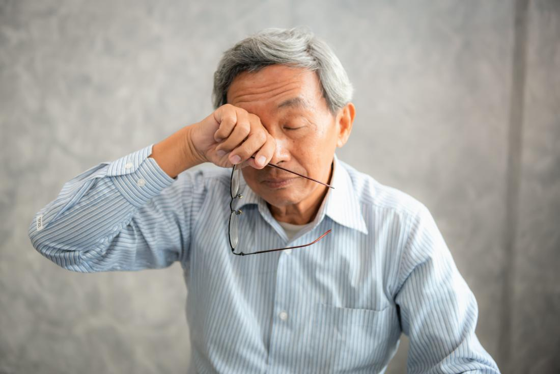 A senior man experiencing steroid side effects holds his glasses and rubs his eyes.