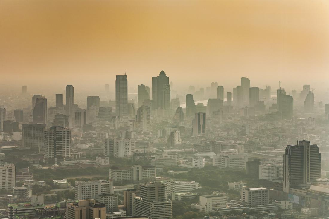 Smog and air pollution in sunset city skyline