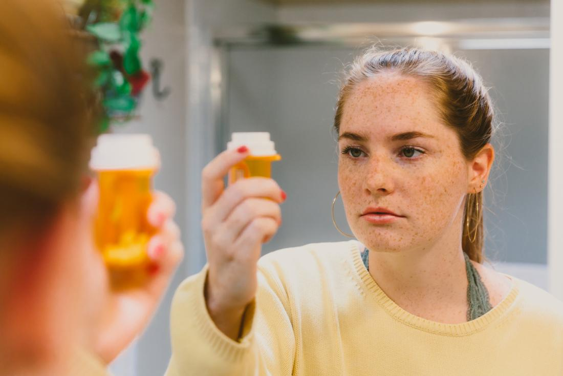 Woman examining medication pot of Guanfacine or Adderall.