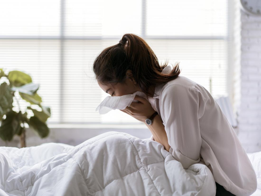 A woman in bed coughing. Symptoms of TB include a bad cough, chest pain, and breathlessness.