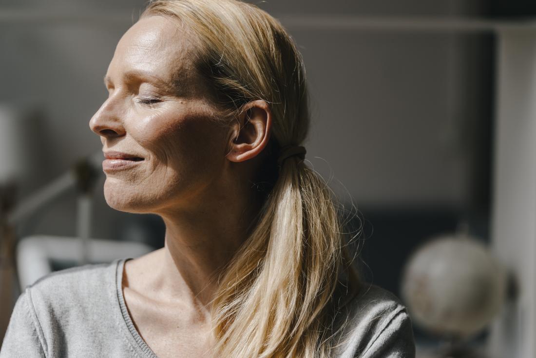 Woman smiling in the sun shine.