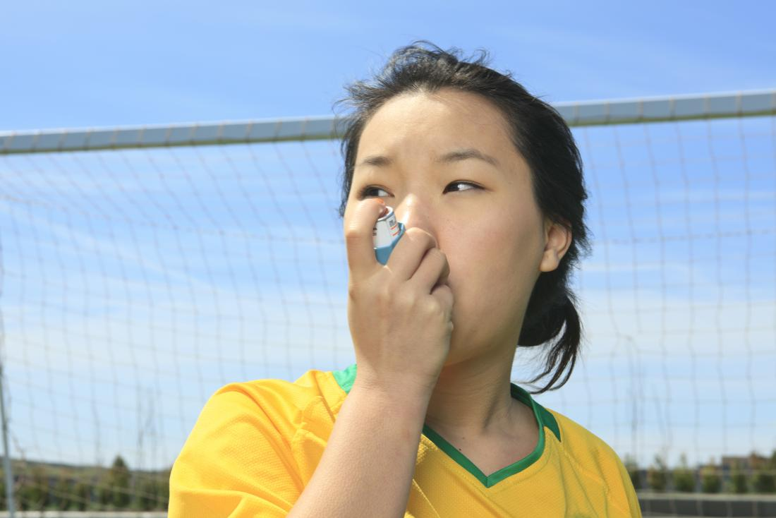 Woman taking inhaler for asthma whilst playing football. Intrinsic and extrinsic asthma have the same symptoms but different triggers