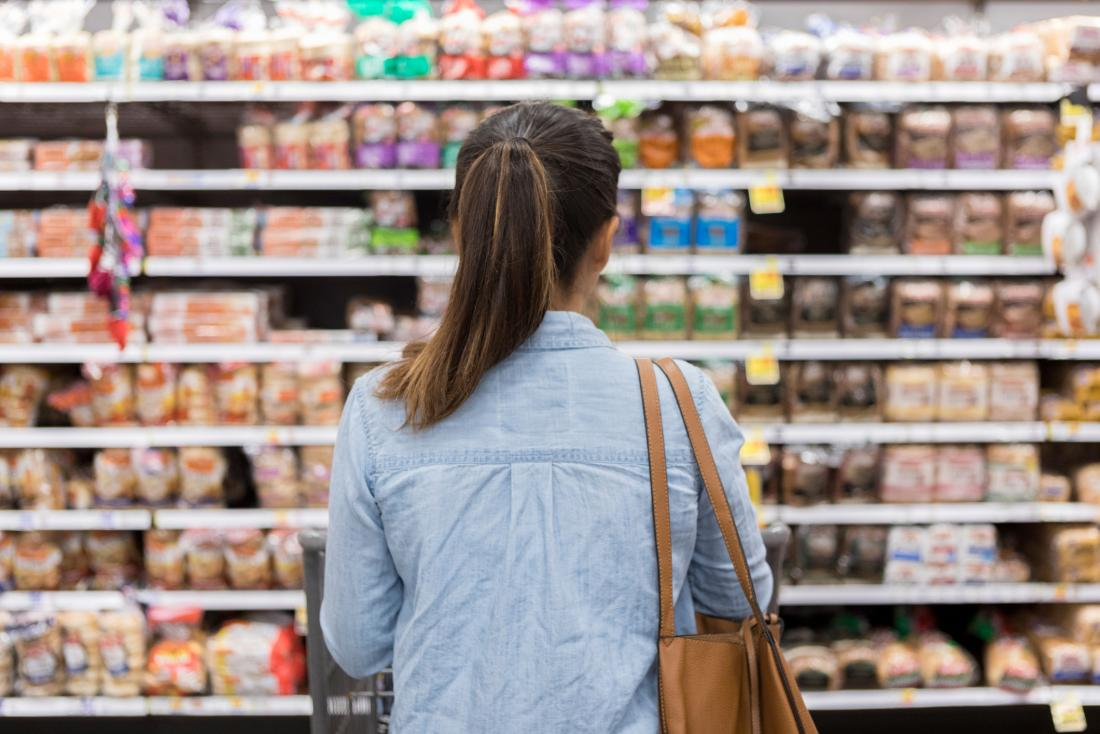 woman looking at processed foods in supermarket aisle, seen from behind