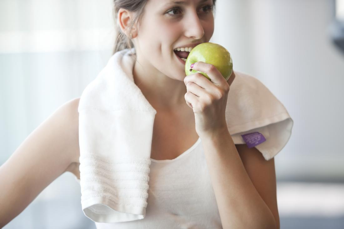 A woman in sports clothes eating an apple.