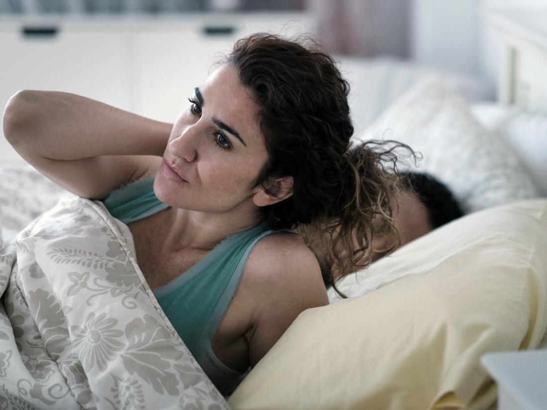 A woman waking up from a bad nights sleep.