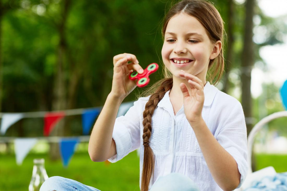 A girl with autism looking at a spinner.