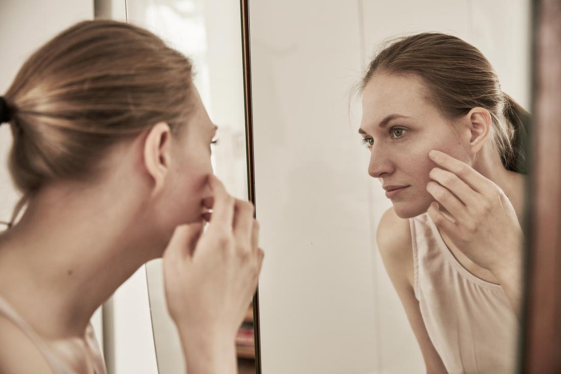 Woman with Argyria looks in the mirror.
