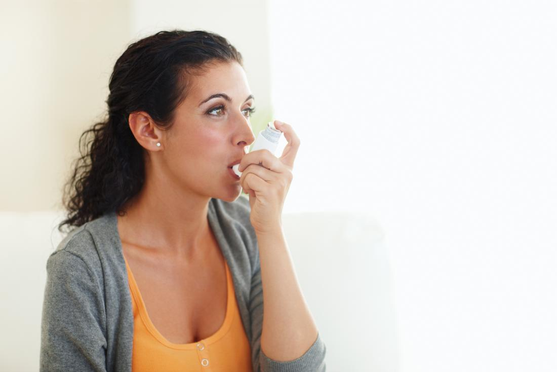 A woman using a bronchodilator. A person can use a bronchodilator to relax the muscles in the airways.