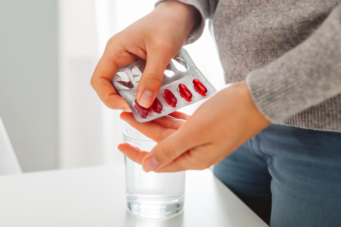 A person popping some Amantadine pills out of a blister pack.