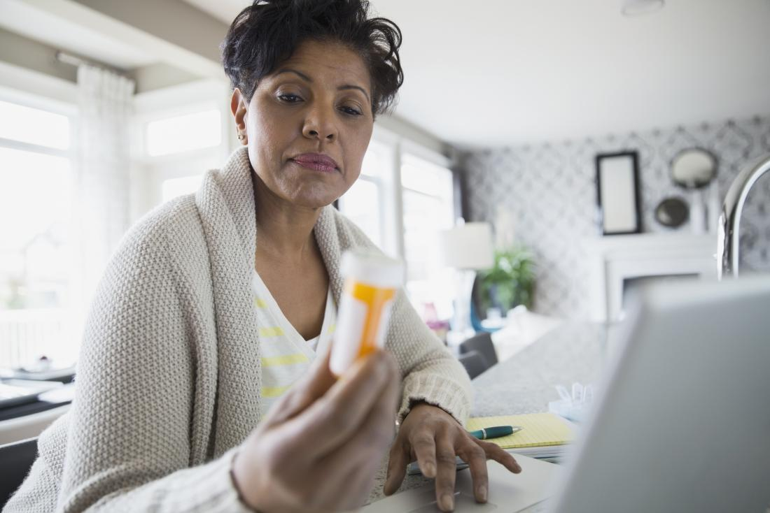 A lady holding a tube of pills wondering the pros and cons of Concerta vs. Ritalin.
