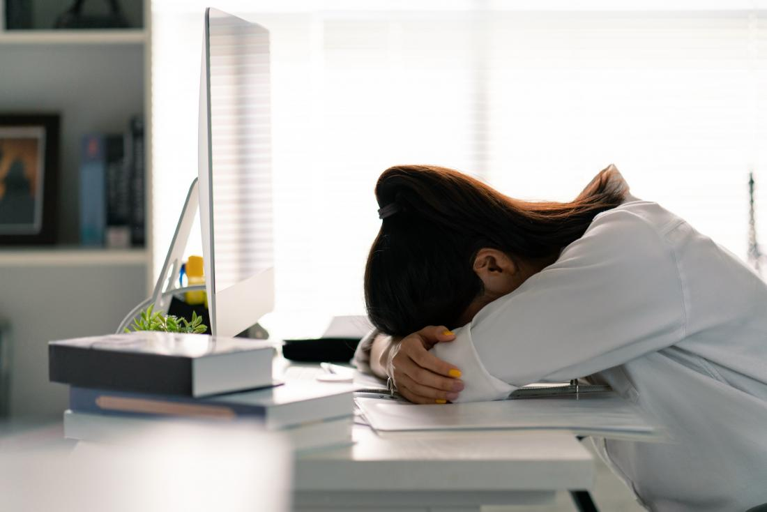 A woman suffering from extreme tiredness at her work desk.