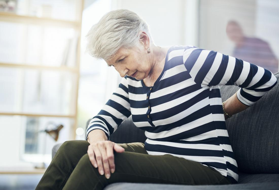 A woman on a sofa suffering from lower back pain and constipation