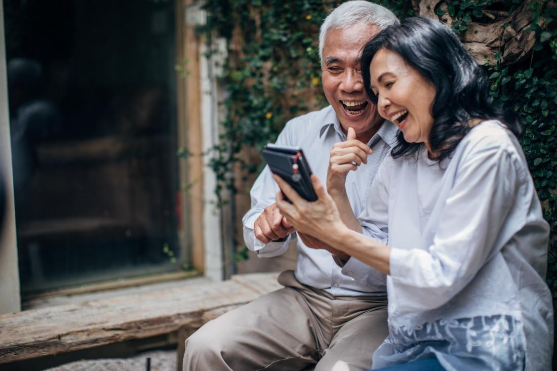 senior couple laughing at a mobile phone