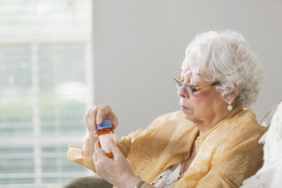 senior woman holding bottle of tablets