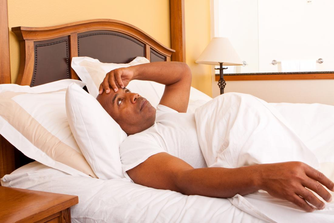 man awake in bed as he can't get out of bed