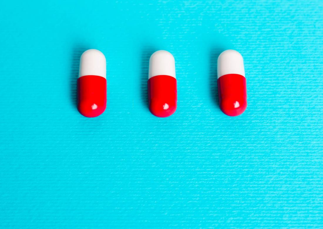 three pills on blue background