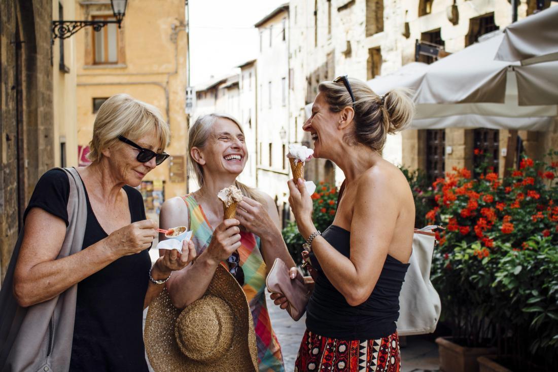 mature female friends enjoying ice cream