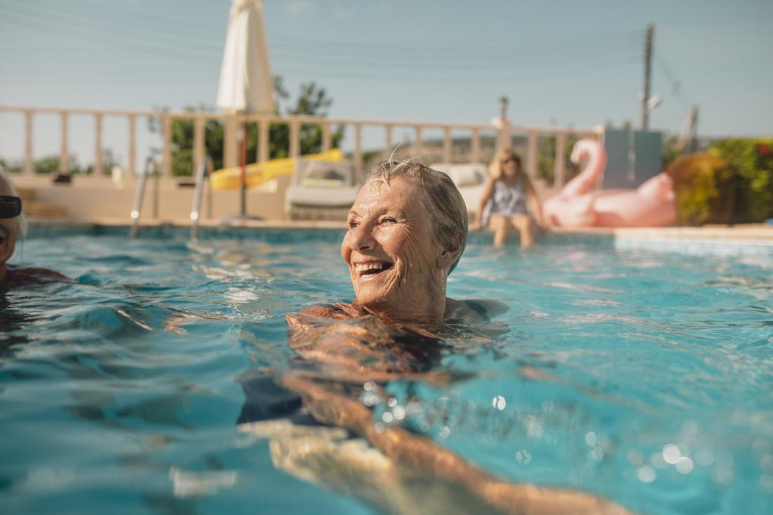 senior woman laughing and swimming