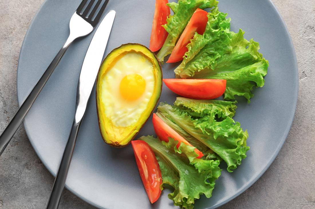salad on a plate next to an egg in an avocado