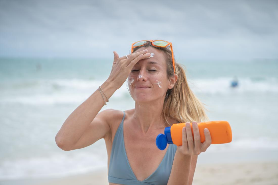 Woman on the beach applies sunscreen to face in addition to using vitamin c serum.