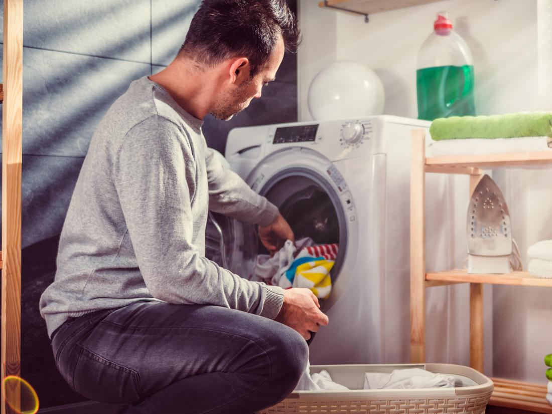a man putting laundry in a washing machine.