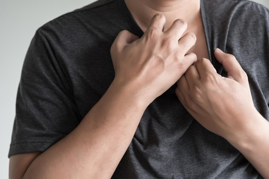 A man scratching his chest because of Keto rash. -